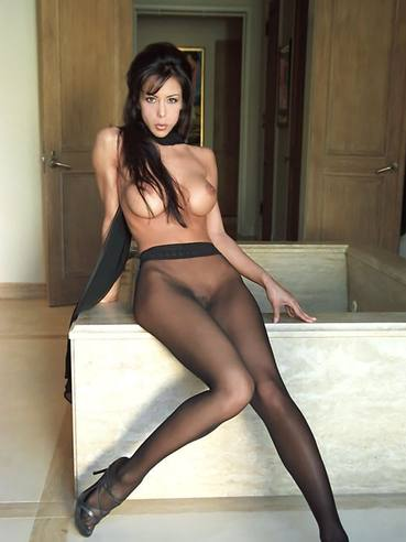 Raunchy brunette Linda in black pantyhose posturing topless on camera taking hot seductive poses.